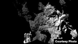 FILE - Rosetta's lander Philae is safely on the surface of Comet 67P/Churyumov-Gerasimenko, as these first two CIVA images confirm. One of the lander's three feet can be seen in the foreground. The image is a two-image mosaic, Nov. 13, 2014. (Courtesy: European Space Agency)
