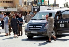 An Islamic State militant uses a bull horn to announce to residents of Tabqa city that Tabqa air base has fallen to Islamic State militants, in nearby Raqqa city, Aug. 24, 2014.