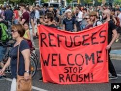 ພວກເດີນຂະບວນ ປະທ້ວງ ຖືປ້າຍ ທີ່ມີຂໍ້ຄວາມວ່າ 'ຍິນດີຕ້ອນຮັບ ຊາວອົບພະຍົບ!' ໃນນະຄອນ Dresden ຢູ່ທາງພາກຕາເວັນອອກ ຂອງເຢຍຣະມັນ, ວັນທີ 29 ສິງຫາ 2015. ສະຖານທີ່ເພິ່ງພາອາໄສແຫ່ງນຶ່ງ ໄດ້ຖືກໂຈມຕີ ໂດຍພວກປະທ້ວງຫົວນິຍົມຂວາຈັດ ໃນນະຄອນ Heidenau ໃກ້ກັບ Dresden ເມື່ອອາທິດແລ້ວນີ້.