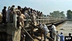 Các nạn nhân lụt dùng gỗ, dây để leo lên chiếc cầu đã bị nước cuốn trôi một số nhịp