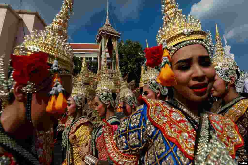 "Para penari tradisional berdiri di dekat kereta kerajaan ""Great Victory Royal Chariot"" yang akan membawa jenazah Raja Bhumibol Adulyadej dalam guci berhias raksasa ke lokasi kremasi di Bangkok, Thailand, 21 September 2017."