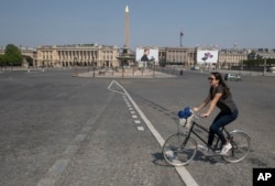 A woman crosses the Concorde square as she rides a bike during a nationwide confinement to counter the new coronavirus in Paris, Friday, April 10, 2020. (AP photo)