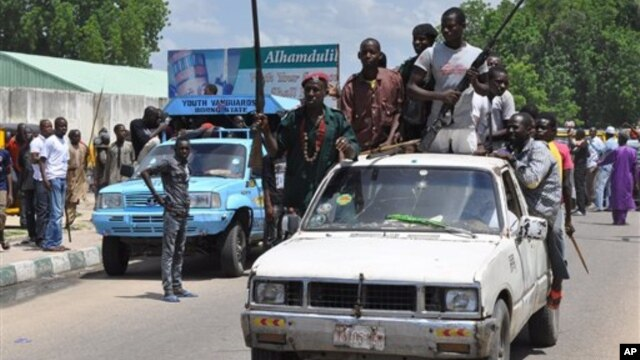 FILE - Vigilantes and local hunters armed with machetes and guns shout slogans as they gather outside the Emir's palace for a royal blessing to fight Islamist Militants in Maiduguri, Nigeria, Sept. 4, 2014.
