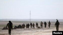 Pasukan Demokratik Suriah berjalan di kawasan yang mereka ambil alih dari ISIS di Hasaka, Suriah, 19 Februari 2016.