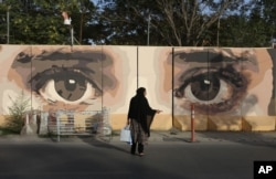 An Afghan woman waits for transportation in front of street art on a barrier wall of the NDS (National Directorate of Security) in Kabul, Aug. 20, 2015.