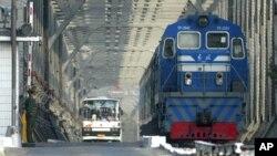 지난 2004년 북한 열차와 버스가 북한과 중국을 잇는 교량을 건너 접경도시 중국 단둥으로 들어오고 있다. (자료사진)