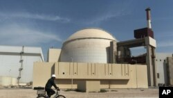 A worker rides a bicycle in front of the reactor building of the Bushehr nuclear power plant. (File)