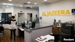 FILE: An employee walks inside an office of Qatar-based Al Jazeera network in Jerusalem, June 13, 2017.