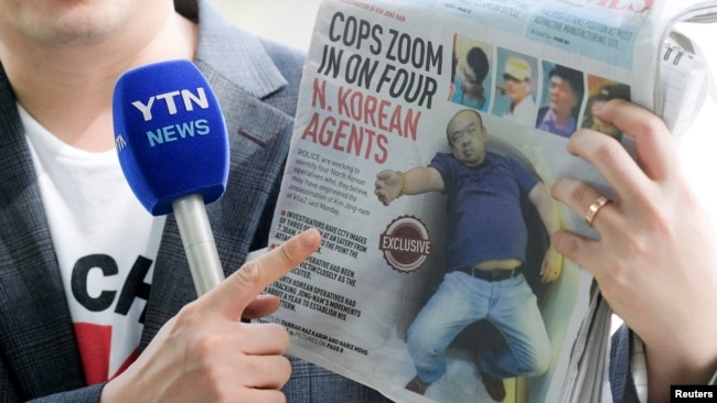 Một phóng viên cầm một tờ báo địa phương, đăng hình ảnh anh trai ông Kim Jong Un sau khi bị tấn công, trong khi đưa tin ở phía trước một nhà xác ở bệnh viện ở Kuala Lumpur nơi xác của ông Kim Jong Nam đang được khám nghiệm hôm 18/2.
