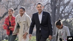 President Barack Obama, with first lady Michelle Obama and daughters Malia, 12, left, and Sasha, 9, right, return to the White House in Washington, 4 Jan 2011
