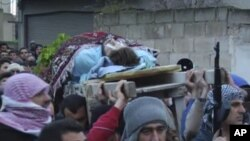 This image taken from video filmed over the past several days by an independent cameraman and made available February 7, 2012 shows a man carried outside in a funeral procession in Homs, Syria.