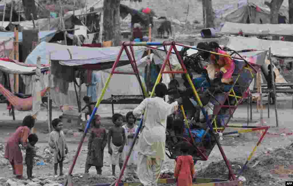 Mali Pakistanci, jedni čekaju, drugi se ljuljaju, u jednom sirotinjskom naselju u Lahore-u.