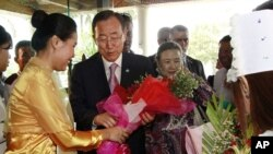 U.N. Secretary-General Ban Ki-moon, center left, and his wife Yoo Soon-taek, center right, receive flowers from a staff upon their arrival at a hotel Sunday, April 29, 2012 in Yangon, Burma.