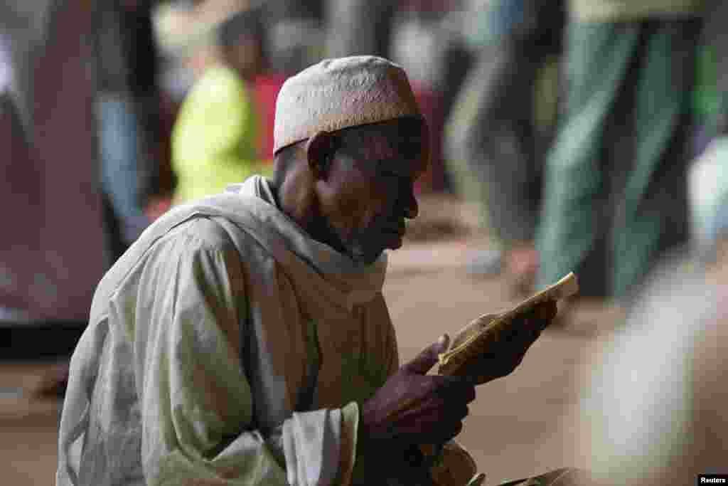 A man prays while reading verses from the Koran in a hangar at the airport of the capital Bangui January 30, 2014. The hangar is used to shelter internally displaced Muslims fleeing the continuing sectarian violence and those waiting to be evacuated by ai