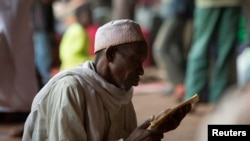 A man prays while reading verses from the Koran in a hangar at the airport of the capital Bangui January 30, 2014. The hangar is used to shelter internally displaced Muslims fleeing the continuing sectarian violence and those waiting to be evacuated. (Photo: Reuters)
