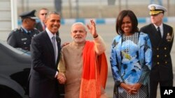 Presiden AS Barack Obama berjabat tangan dengan Perdana Menteri India Narendra Modi yang diapit ibu negara AS Michelle Obama di New Delhi (25/1).
