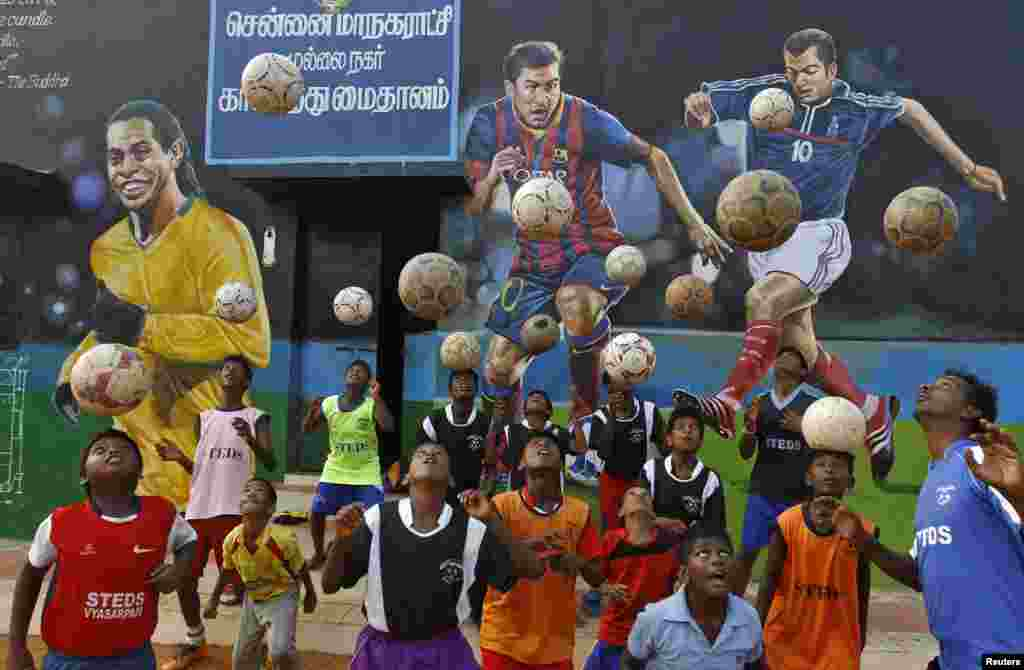 Boys practice during a heading drill in front of murals of (L-R), Brazil's Ronaldinho, Argentina's Lionel Messi and France's Zinedine Zidane, at a playground in the southern Indian city of Chennai.