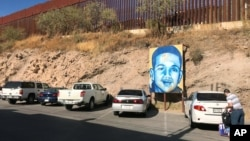 A portrait of 16-year-old Mexican youth Jose Antonio Elena Rodriguez, who was shot and killed in Nogales, Sonora, Mexico, is displayed on the street where he was killed that runs parallel with the U.S. border, Dec. 14, 2017. A U.S. border patrol agent is going on trial for second-degree murder in U.S. District Court in Tucson, March 20, 2018.