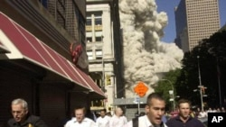 People run from the collapse of World Trade Center Tower in New York City on September eleventh, 2001