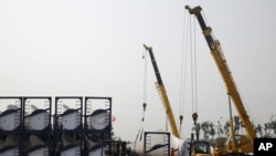 Workers prepare to lift a giant blade to be used as part of wind turbines at the Vestas Wind Technology (China) Co. Ltd. factory in Tianjin, China, September 14, 2010.