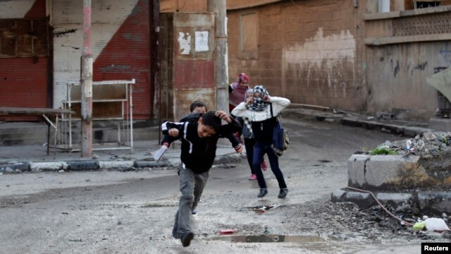 FILE - Children run across a street to avoid snipers in Deir al-Zor, eastern Syria, Feb. 16, 2014.