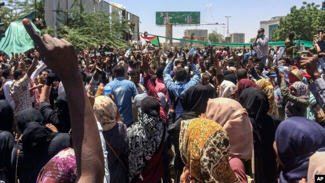 Protesters rally in front of the military headquarters in the capital Khartoum, Sudan, Monday, April 8, 2019.