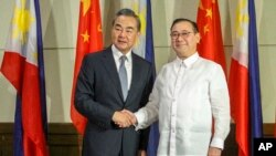New Philippine Foreign Affairs Secretary Teodoro Locsin Jr., right, and visiting Chinese Foreign Minister Wang Yi shake hands during the latter's courtesy call in Davao city, southern Philippines Monday, Oct. 29, 2018.
