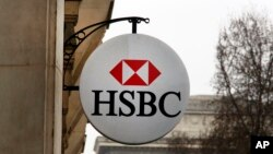 FILE - The logo of HSBC Bank is displayed on the facade of HSBC France headquarters on the Champs Elysees in Paris, Feb. 9, 2015.