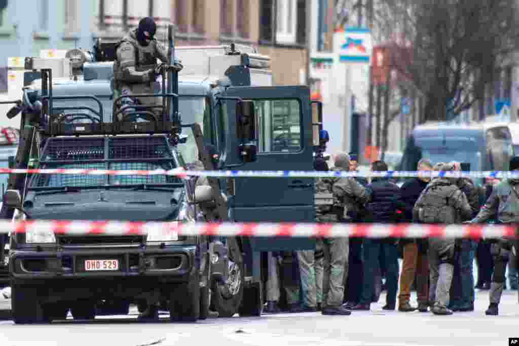 A member of the special forces police installs equipment on a van in Ghent, western Belgium. Four armed men have entered an apartment, and police have blocked off a wide perimeter around the area. Police said that three hours after the men entered the apartment it was still unclear whether they had taken any hostages.