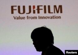 Siluet seorang pria tergambar di bawah logo Fujifilm Holdings saat berlangsungnya konferensi pers di Tokyo, Jepang, 31 Januari 2018. (REUTERS/Kim Kyung-Hoon)