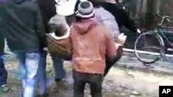 星期一在霍姆斯示威活動的傷者被抬離示威現場