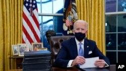 ប្រធានាធិបតីសហរដ្ឋអាមេរិកលោក Joe Biden ក្នុងអំឡុងពេលចុះហត្ថលេខាលើបទបញ្ជានីតិប្រតិបត្តិជាលើកដំបូងរបស់លោក ក្នុងនាមជាប្រធានាធិបតីថ្មីរបស់សហរដ្ឋអាមេរិក ក្នុងការិយាល័យប្រធានាធិបតីនៅសេតវិមាន ថ្ងៃពុធ ទី២០ ខែមករា ឆ្នាំ២០២១។