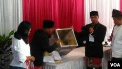 Petugas TPS 28 Cilandak Barat, Jakarta Selatan, memperlihatkan kotak suara yg kosong, Rabu (19/4). TPS ini adalah tempat calon gubernur Anies Baswedan menggunakan hak pilihnya. (Foto VOA/Andylala)