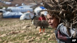 FILE - An Iraqi Yazidi girl carries wood in a conflict area in northern Iraq. The United Nations Children's Fund says one in four shool-aged children in conflict areas is not in school.