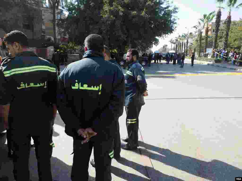 Paramedics wait at the explosion location in Giza, Egypt, Dec. 9, 2016. (H. Elrasam/VOA)