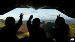 지난해 12월 미국 공군과 일본 항공자위대원들이 북마리아나 제도 파간섬 주민들을 위한 크리스마스 선물을 공중에서 투하한 후 주민들을 향해 손을 흔들고 있다. (자료사진)
