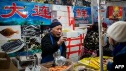 资料照:北京一家海鲜市场的小贩正在向顾客兜售水产品。(2020年1月15日)