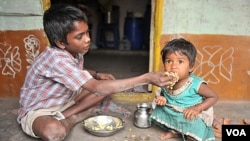 Seorang anak laki-laki menyuapi adiknya di kawasan miskin di Hyderabad, India. PM Manmohan Singh mengatakan tingginya angka malnutrisi merupakan aib negara (foto:dok).