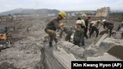 Workers recover cement blocks from flood-damaged areas in Onsong, North Hamgyong Province, North Korea.