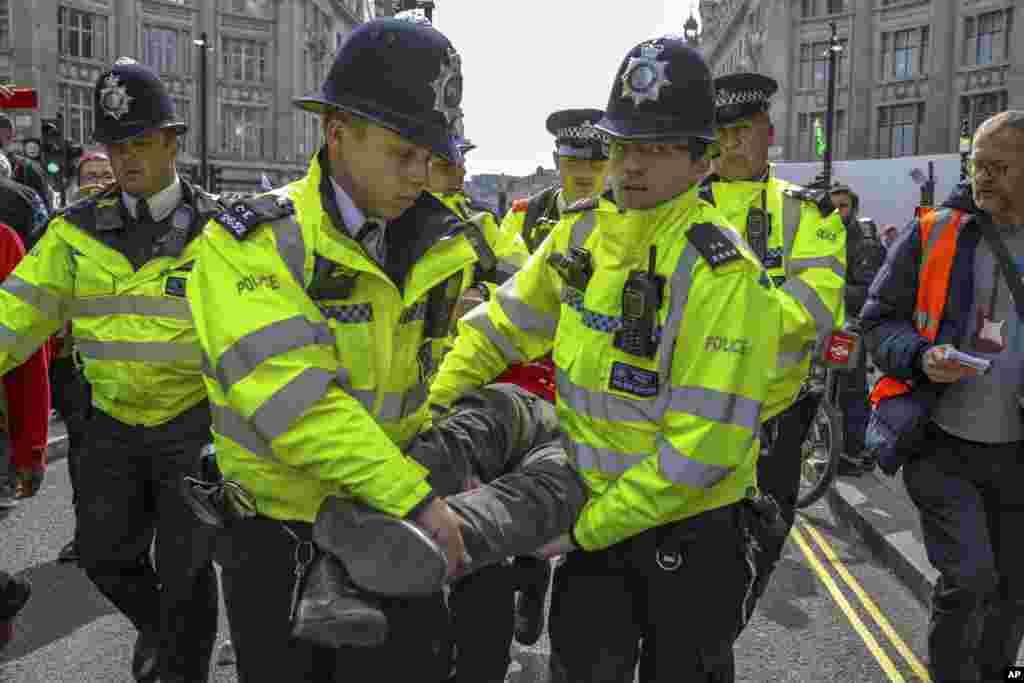 پلیس یک معترض به دولت بریتانیا توسط پلیس برده می شود. معترضان می گویند بریتانیا تغییرات آب و هوایی و خطرات ناشی از آن را جدی نمی گیرد.