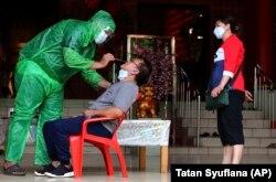 Seorang petugas kesehatan melakukan tes usap COVID-19 kepada seorang pengunjung di sebuah kelenteng di Tangerang, Sabtu, 6 Februari 2021. (Foto: Tatan Syuflana/AP)