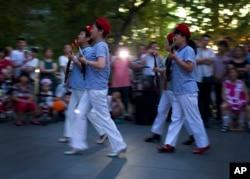 中国妇女在北京一座商城外的广场上随着革命歌曲跳舞,她们手中拿着玩具枪道具。(2014年1月29日)