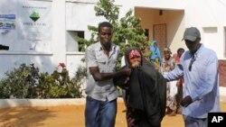 자살 폭탄 공격이 일어난 소말리아 모가디슈에 위치한 빌리지 식당 근처 현장에서 부상당한 여인을 부축하는 경찰 관계자들