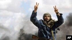 """Borac iz pobunjeničkih postrojbi viče """"Alah Akbar!"""" pred uništenim vozilima Gadafijeve vojske"""