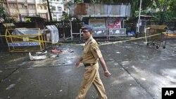 图为一名警察7月15日走过孟买一处爆炸现场