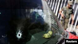 A car windshield with a bullet hole is seen at a crime scene outside the San Juan De Dios Hospital, Guatemala City, March 10, 2015.