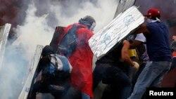 Estudiantes se protegen de los gases lacrimógenos lanzados por la Guardia Nacional al finalizar las protestas del domingo, en Caracas .