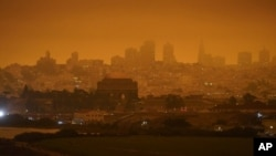 FILE - In this Sept. 9, 2020, file photo, taken at 11:18 a.m., is a dark orange sky above Crissy Field and the city caused by heavy smoke from wildfires in San Francisco. (AP Photo/Eric Risberg, File)
