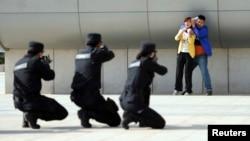 2014年5月7日,中國鄭州警方在火車站舉行反恐演習。武裝警察舉槍瞄準一個劫持婦女的恐怖分子的扮演者