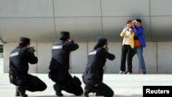 2014年五月7日,中国郑州警方在火车站举行反恐演习。武装警察举枪瞄准一个劫持妇女的恐怖分子的扮演者
